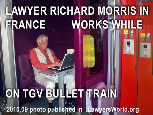 Photo of Richard Morris working on his laptop commputer while on TGV French Bullet  Train wainting to return to Paris